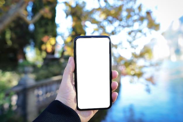 緑と湖の自然の背景と空白の画面で携帯電話を持っている手のモックアップ画像