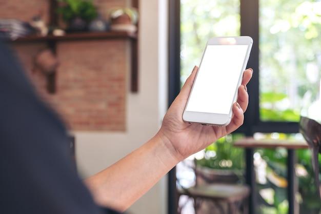 Макет изображения руки, держащей мобильный телефон с пустой белый экран в кафе