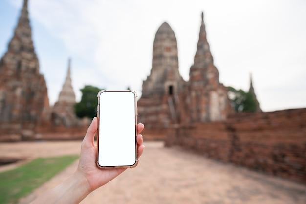 Изображение макета руки, держащей мобильный телефон с пустым белым экраном с пагодой.