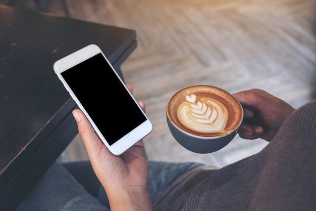 Макет изображения рук, держащих белый мобильный телефон с пустым экраном во время питья кофе