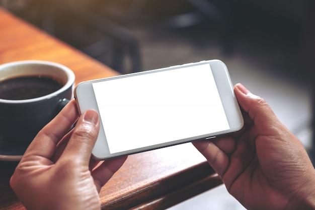 손을 잡고 나무 테이블에 커피 컵을보고 가로로 빈 화면이 흰색 휴대 전화를 사용의 모형 이미지
