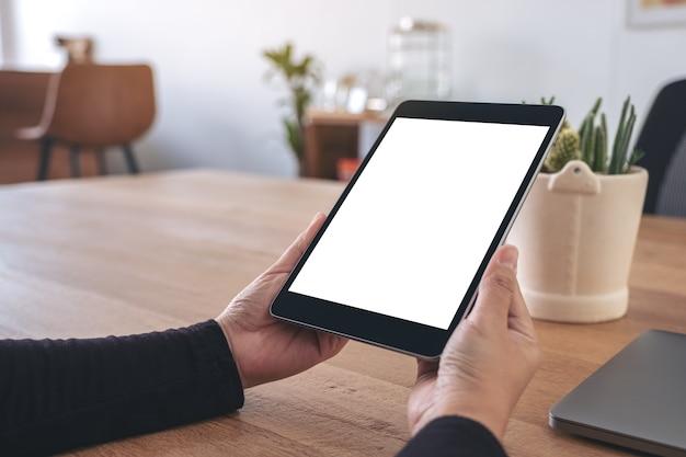 Макет изображения рук, держащихся и использующих черный планшетный пк с пустым белым экраном рабочего стола с ноутбуком на деревянном столе в офисе