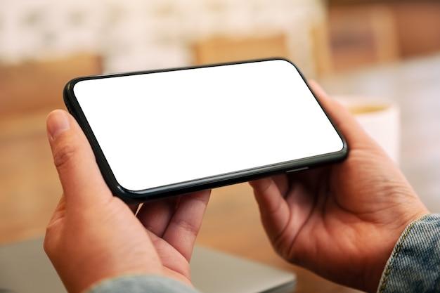 Макет изображения рук, держащих черный мобильный телефон с пустым экраном рабочего стола по горизонтали с чашкой кофе на столе