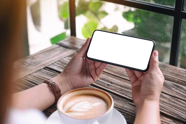 탁자 위에 커피 컵이 있는 빈 데스크탑 화면이 있는 검은색 휴대폰을 들고 있는 손의 흉내낸 이미지