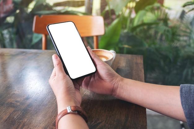 탁자 위에 노트북과 커피 컵이 있는 빈 데스크탑 화면이 있는 검은색 휴대폰을 들고 있는 손의 흉내낸 이미지