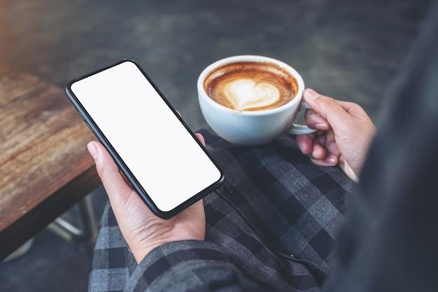 Макет изображения рук, держащих черный мобильный телефон с пустым экраном во время питья кофе в кафе