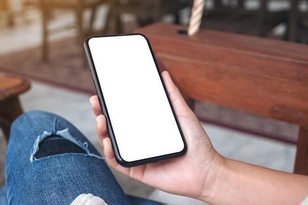 Макет изображения рук, держащих черный мобильный телефон с пустым белым экраном, сидя в кафе
