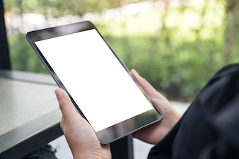 Mockup image of hands holding black tablet pc with blank white desktop screen on the table
