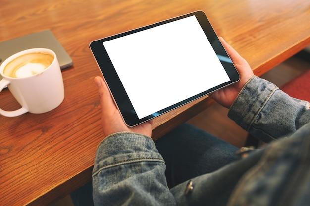 Макет изображения рук, держащих черный планшетный пк с пустым белым экраном по горизонтали с чашкой кофе на деревянном столе
