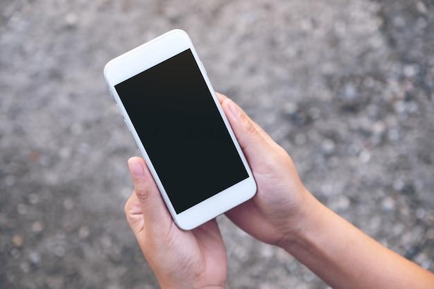 Макет изображения рук, держащих белый мобильный телефон с пустым черным экраном