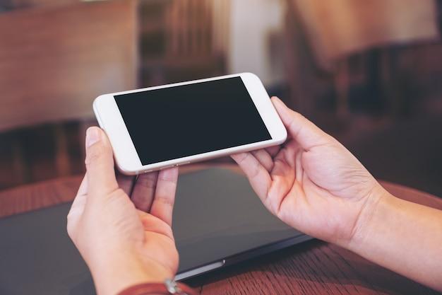 탁자 위에 노트북 컴퓨터가 있는 빈 데스크탑 화면이 있는 흰색 휴대폰을 들고 있는 손의 흉내낸 이미지