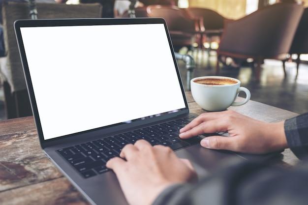 Макет изображения рук, использующих и печатающих на ноутбуке с пустым белым экраном рабочего стола с чашкой кофе на деревянном столе в кафе