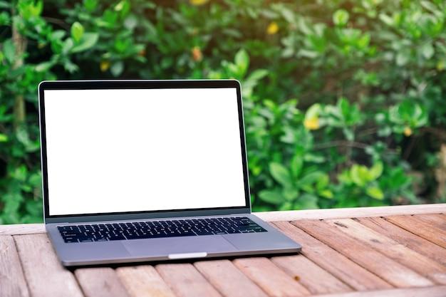 Макет изображения портативного компьютера с пустым белым экраном рабочего стола на деревянном столе