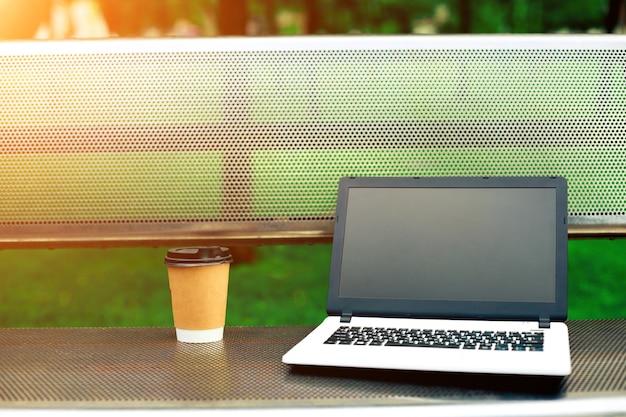 自然の屋外公園の金属製のベンチに空白の黒い画面とコーヒーカップとラップトップのモックアップ画像。フリーランスの仕事..サンフレア