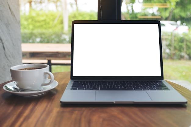 Макет изображение ноутбук с пустой белый рабочий стол на деревянный стол в кафе
