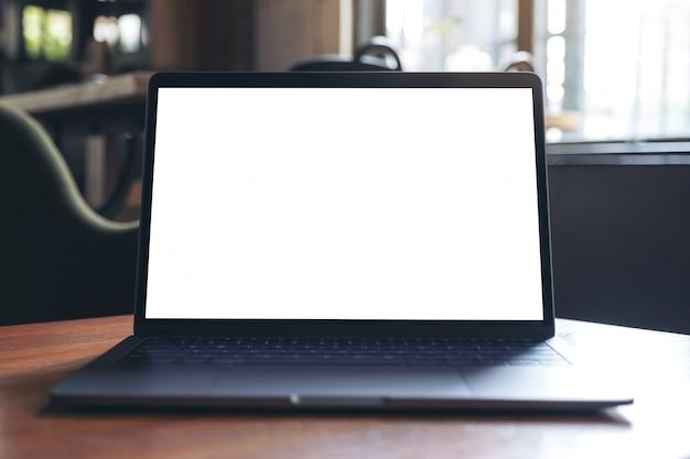 カフェの木製テーブルに空白の白いデスクトップ画面を持つノートパソコンのモックアップ画像