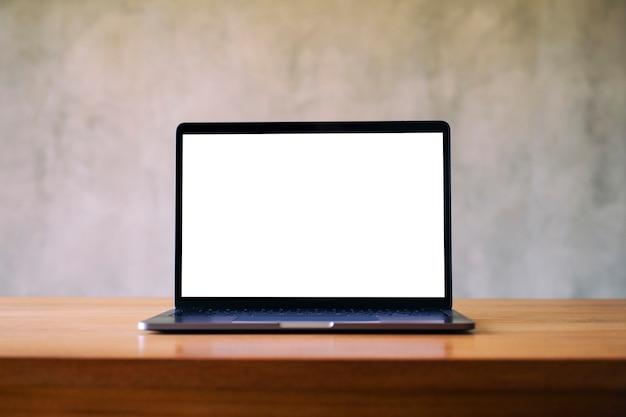 콘크리트 벽 배경이 있는 나무 테이블에 빈 흰색 데스크탑 화면이 있는 노트북의 모형 이미지
