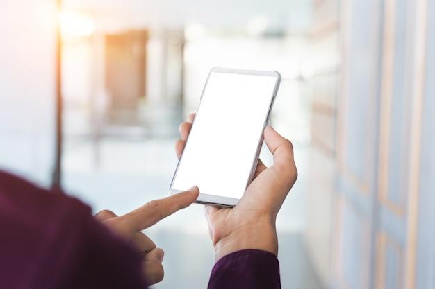 Макет изображение руки человека, проведение белый мобильный телефон с пустой экран технологии.