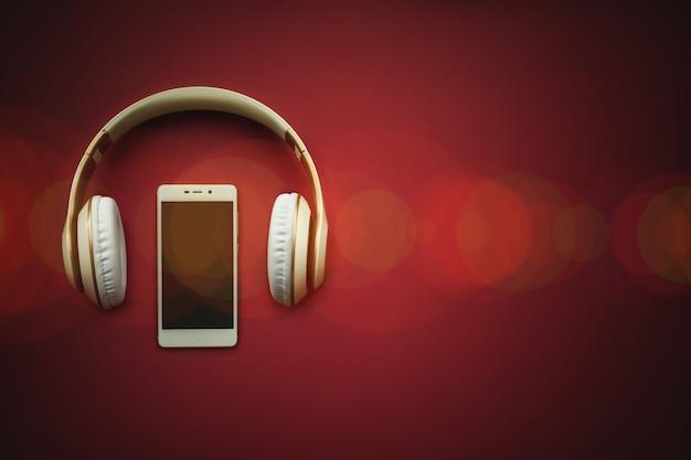 빈 검은색 화면과 보케가 있는 빨간색 배경에 헤드폰이 있는 흰색 휴대폰의 모형 이미지.