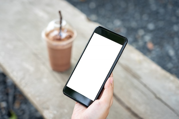 Изображение макета руки женщины держа мобильные смартфоны изолировало белый экран