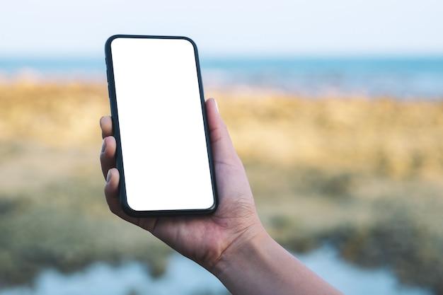 ビーチと海のそばの空白のデスクトップ画面で黒い携帯電話を持っている女性の手のモックアップ画像