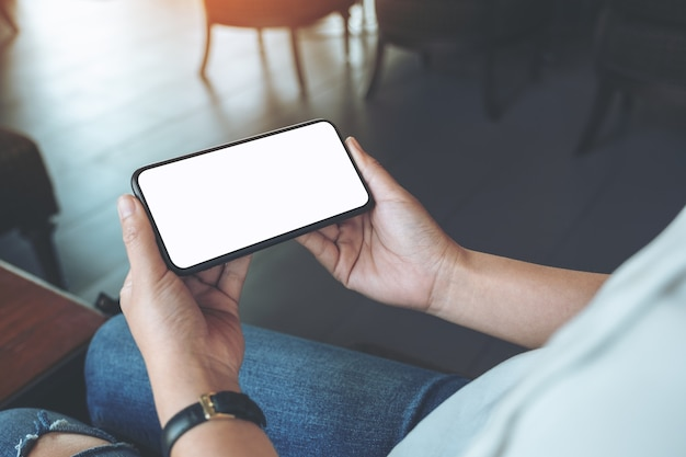 Макет изображения рук женщины, держащей черный мобильный телефон с пустым белым экраном по горизонтали в кафе