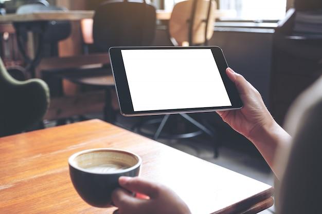 Макет изображения женских рук, держа черный планшетный пк с пустой белый экран с чашкой кофе на деревянный стол в кафе