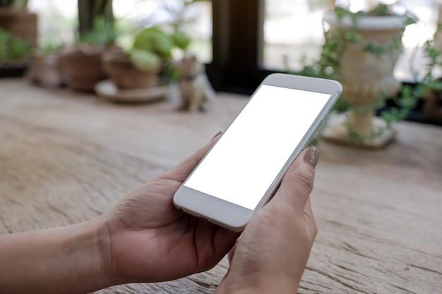Макет изображения женских рук, держа мобильный телефон с пустой белый экран на деревянный стол в старинном кафе