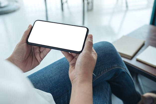 Mockup image of a woman holding black mobile phone with blank desktop screen horizontally