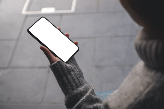 Mockup image of a woman holding black mobile phone with blank desktop screen in the outdoors