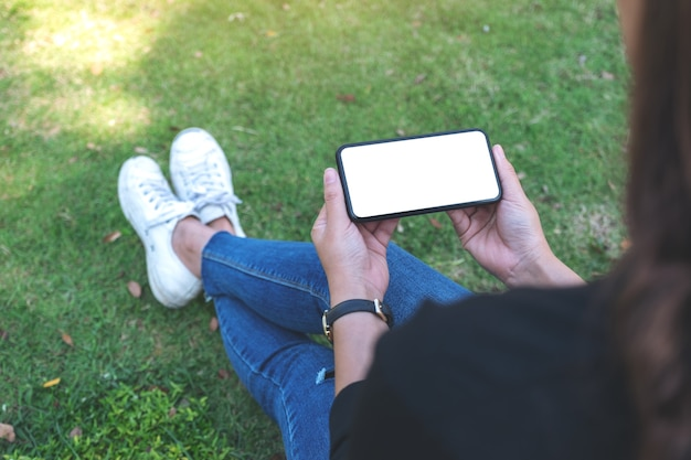 Mockup image of a woman holding black mobile phone with blank white screen horizontally while sitting in the outdoors