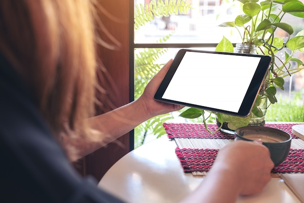 Mockup image of a woman holding black tablet pc with blank white screen