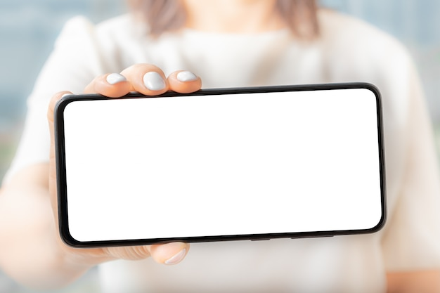 Mockup image of a woman holding and showing black mobile phone with blank screen.