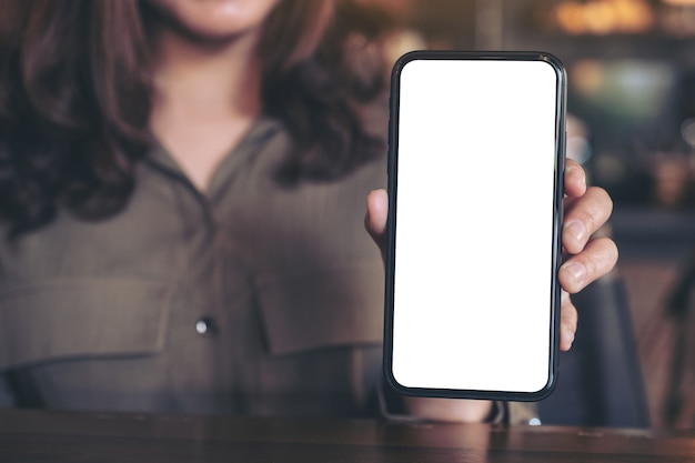 Mockup image of a woman holding and showing black mobile phone with blank white screen on the table in modern cafe