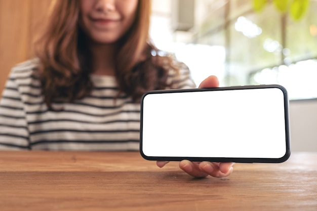 Mockup image of a woman holding and showing white mobile phone with blank screen horizontally on wooden table