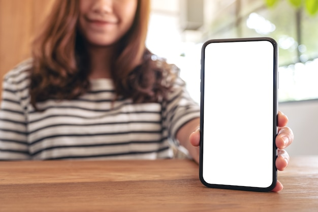 Mockup image of a woman holding and showing white mobile phone with blank screen on wooden table