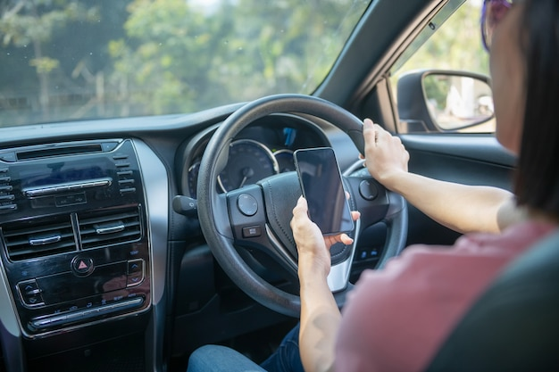 Mockup image of a woman holding and using mobile phone with blank screen while driver a car, for gps, lifestyles photo in car, interior, front view. with woman hand holding phone.