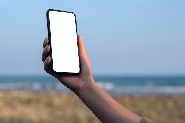 Mockup image of woman's hand holding black mobile phone with blank desktop screen by the beach and sea with blue sky background