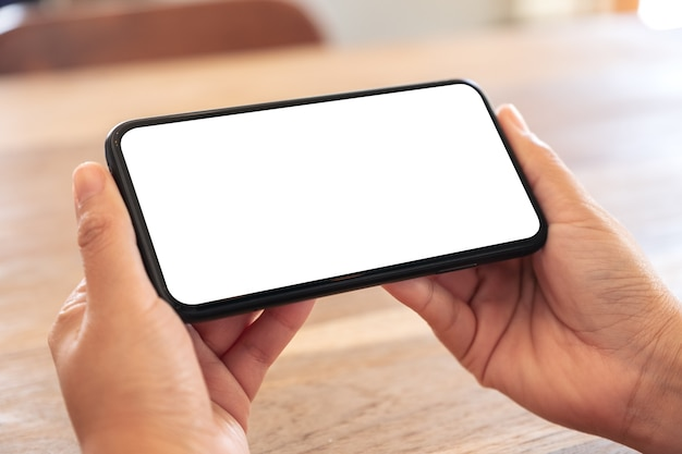 Mockup image of woman's hands holding black mobile phone with blank white screen horizontally on wooden table