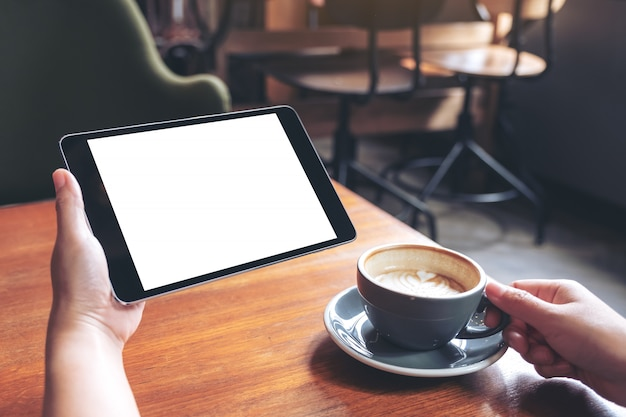 Mockup image of woman's hands holding black tablet pc with blank white screen with coffee cup on wooden table in cafe