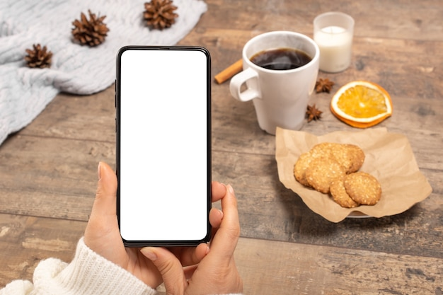 Mockup image of woman's hands holding cell mobile phone with blank screen on table in cafe.