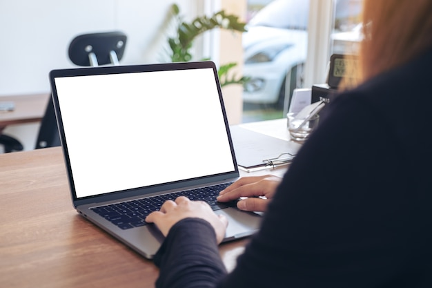 Mockup image of a woman using and typing on laptop with blank white desktop screen