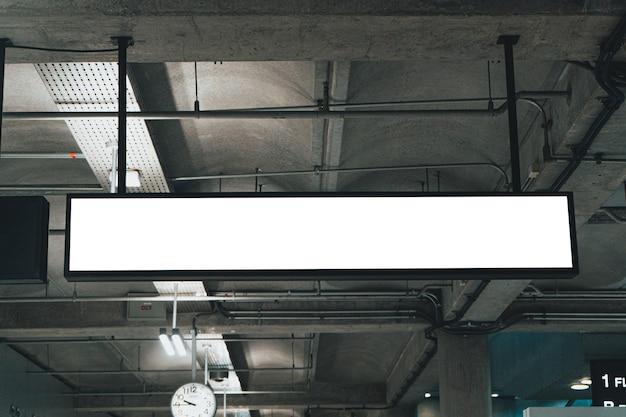 Мокап крытый подвесной знак в здании аэропорта световой знак