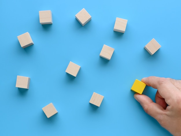 Mockup of joining a team, recruitment business, social network, leadership, team building concepts. hand moves a wooden cube to the group of cubes on blue background. top view