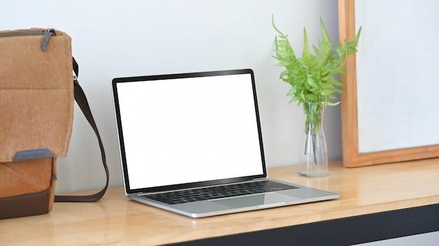 나무 테이블에 이랑 노트북, 가방, 화이트 보드 및 식물 장식.