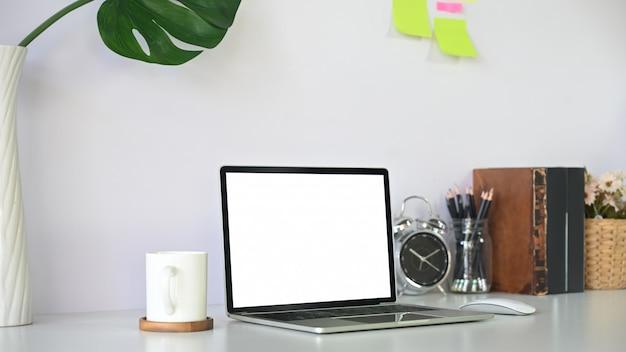 책, 커피, 연필 홀더 및 알람 시계 작업 영역에 모형 노트북 컴퓨터.