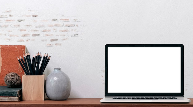Портативный компьютер макета с пустым экраном и поставками на деревянном столе и старой кирпичной стене, космосе экземпляра.