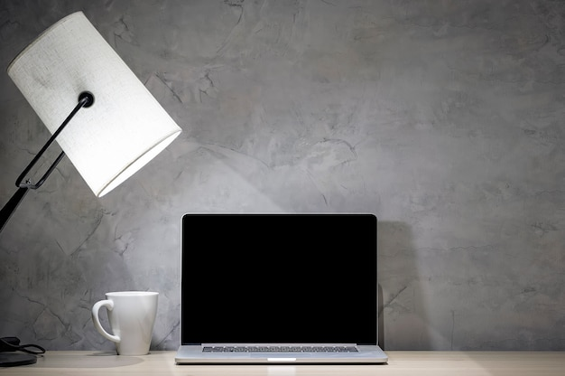 Mockup laptop computer with table lamp and white mug on wood