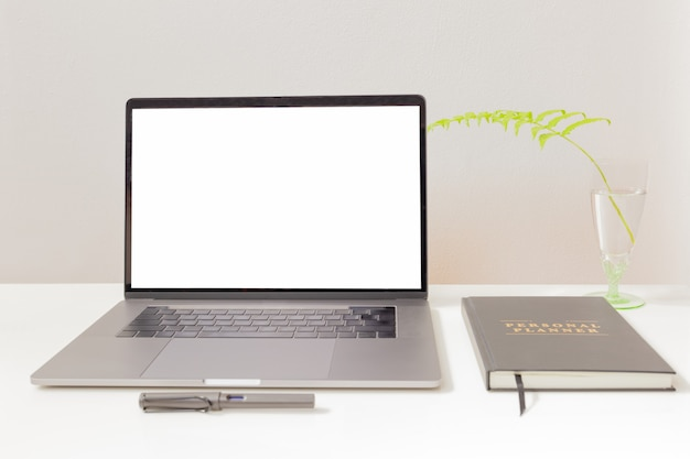 Mockup of laptop and pen with notebook on white table.