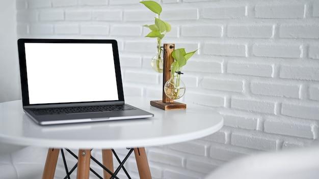 Пустой пустой экран ноутбука макета с вазой лампочки на белом современном столе в кафе